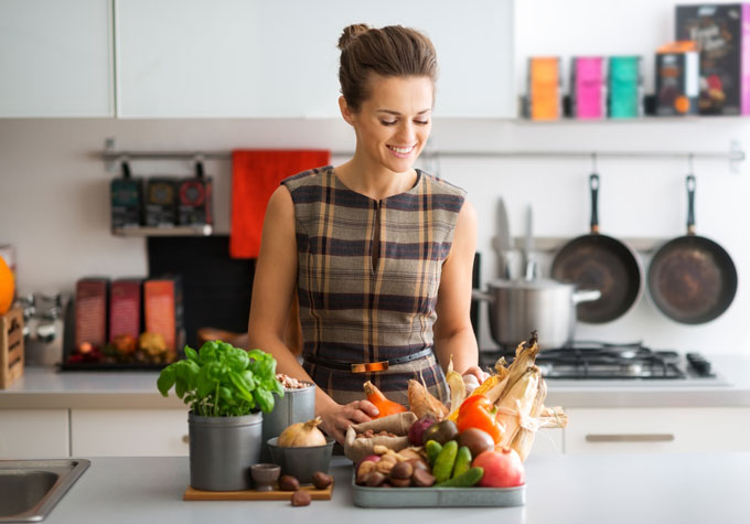 食材が置いてあるキッチンの前に立つ女性
