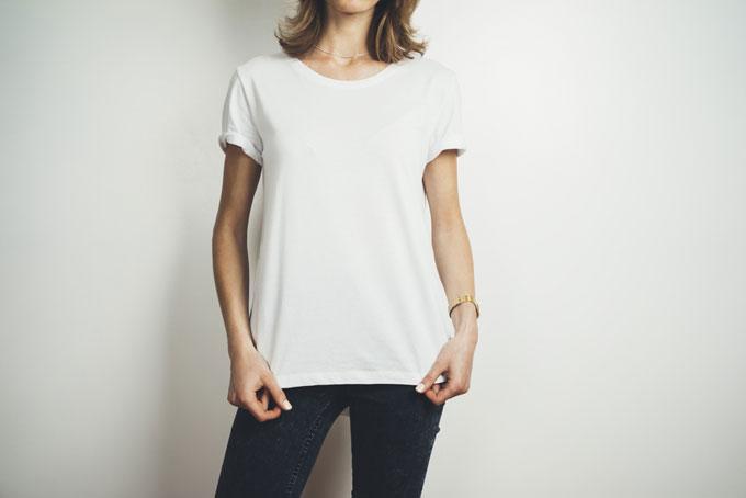白いTシャツの裾を持っている女性の画像