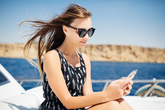 船でスマホを見る女性の画像
