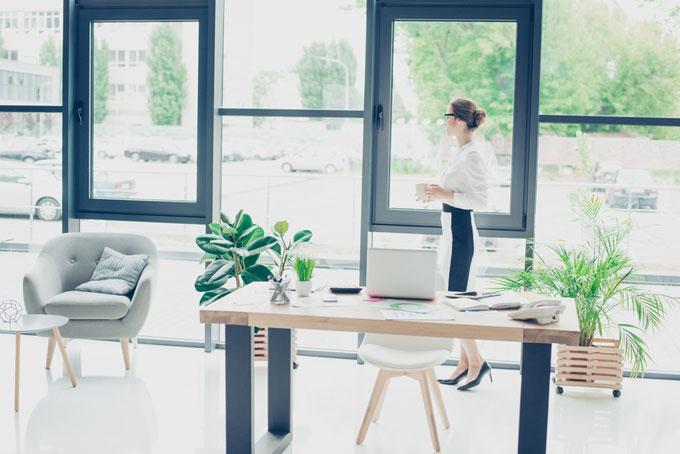 清潔なオフィスで外を見て立っている女性