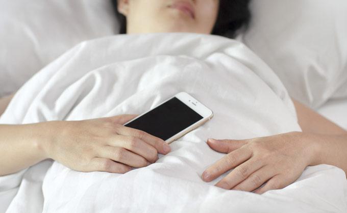 スマートフォンを持ったまま寝ている女性の画像