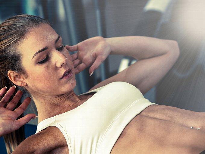 自分の腹筋を見つめる女性