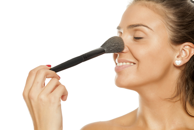 鼻にメイクブラシをあてている女性の画像