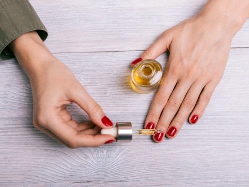 ネイル美容液を塗る女性の手元