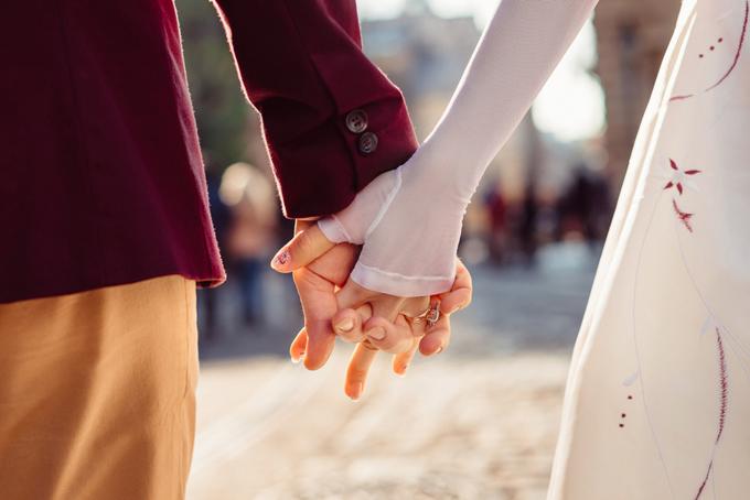 手をつないでいるカップルの手元
