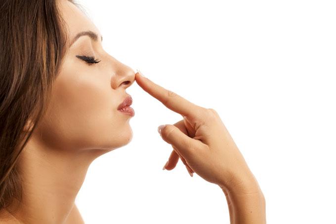 鼻を指先で押さえている女性の横顔の画像