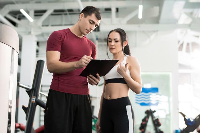 男性のトレーナーと話す女性の画像