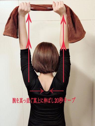タオルを持って腕を上に伸ばす