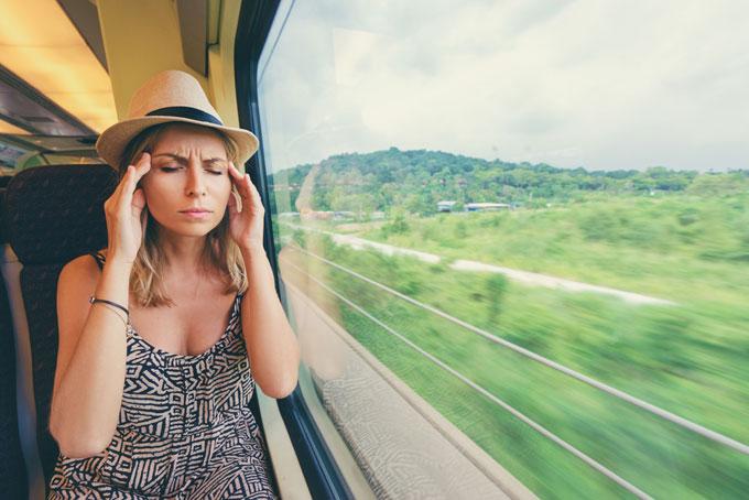 電車の座席で頭を押さえている女性の画像
