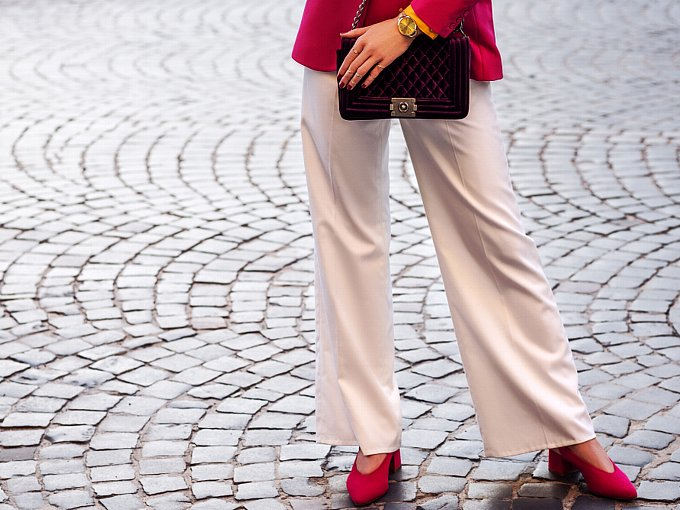 薄いピンクのワイドパンツをはく女性