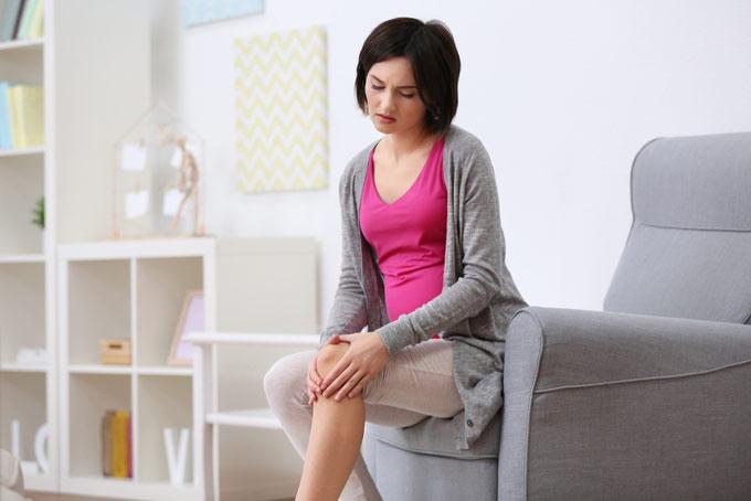 ひざをおさえている女性の画像