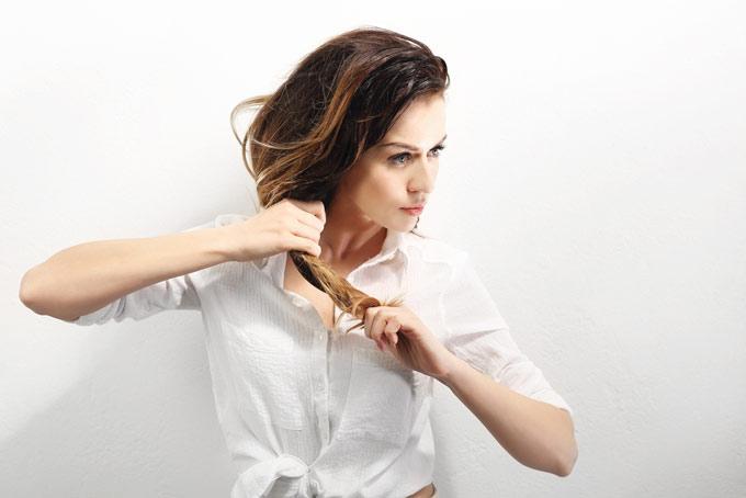髪を手でまとめている女性の画像