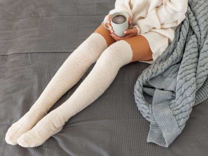 ベッドの上でくつろぐ靴下を履いた女性