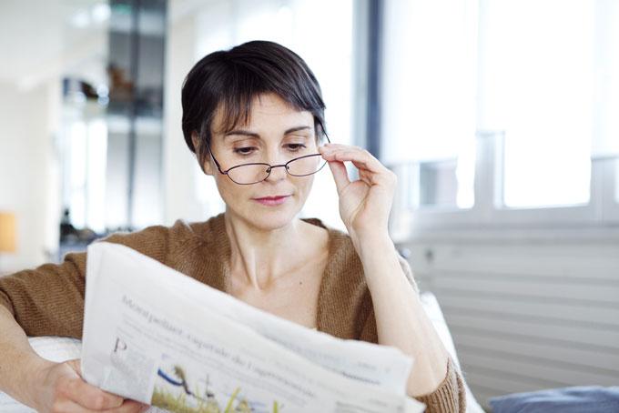 老眼鏡をかけて新聞を読む女性の画像