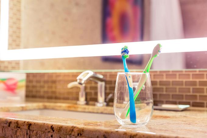 洗面所の透明なコップに入った歯ブラシ2本