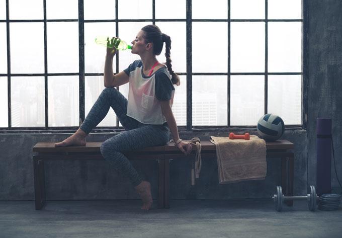 椅子に座って水分補給している女性