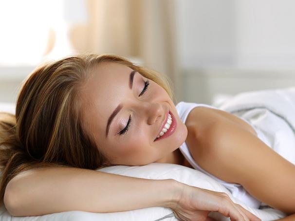 笑顔で寝ている女性の画像
