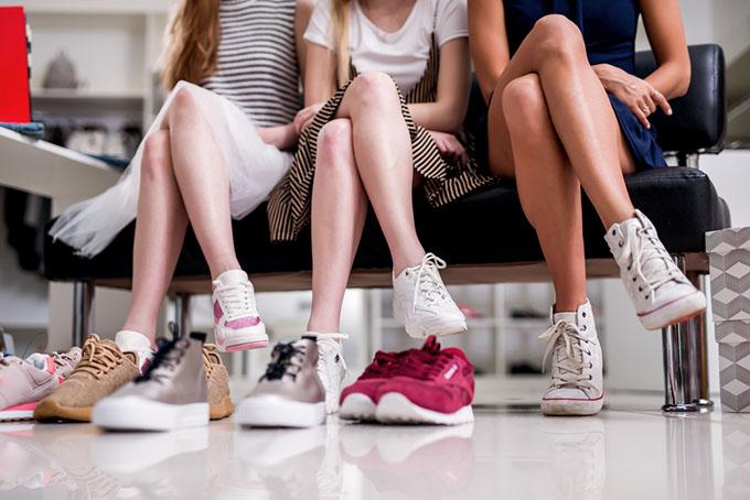 3人の女性はスニーカーを履いて座っている脚元画像