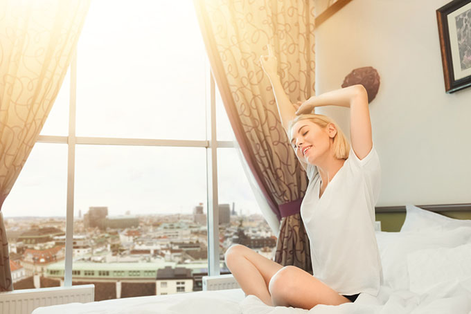 朝ベッドから起きて伸びをしている女性