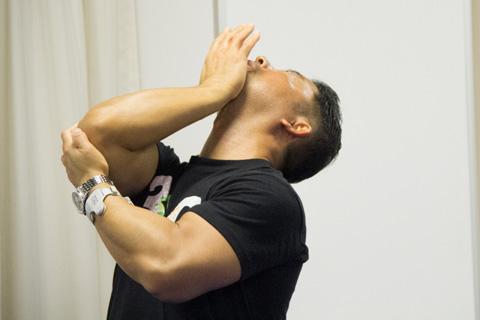 桑原先生が右手の平をあご下に当てて顔を押し上げているポーズ