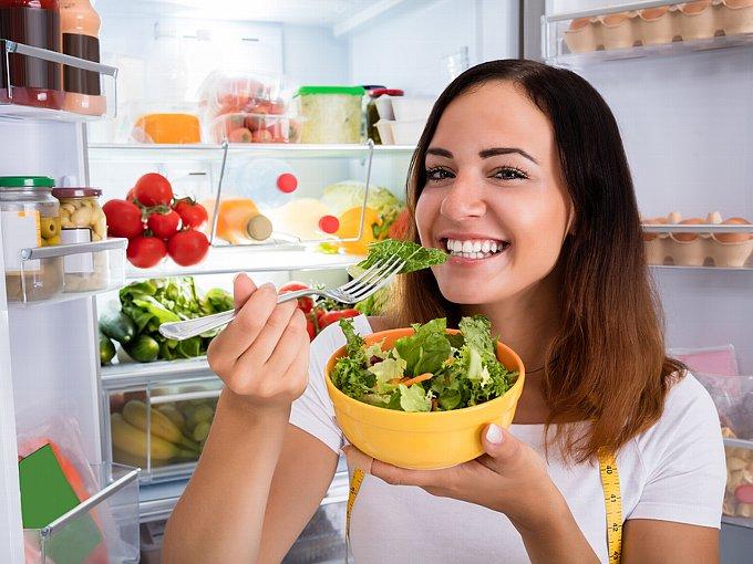 冷蔵庫の前で野菜を食べる女性