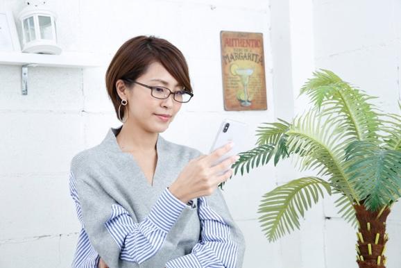 メガネをかけてスマホを見る坂元さん