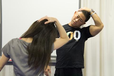 桑原先生が勝ててを側頭部に当て、首を横に倒しているストレッチ