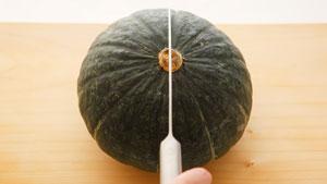 かぼちゃをへたの上から切っている写真