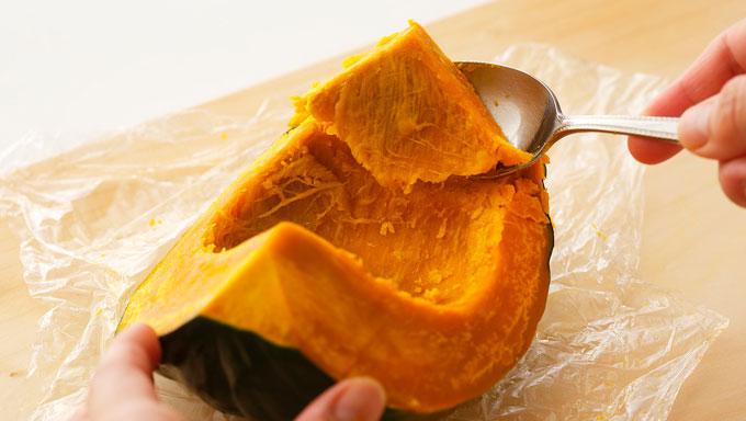 スプーンでかぼちゃの果肉を取っている写真