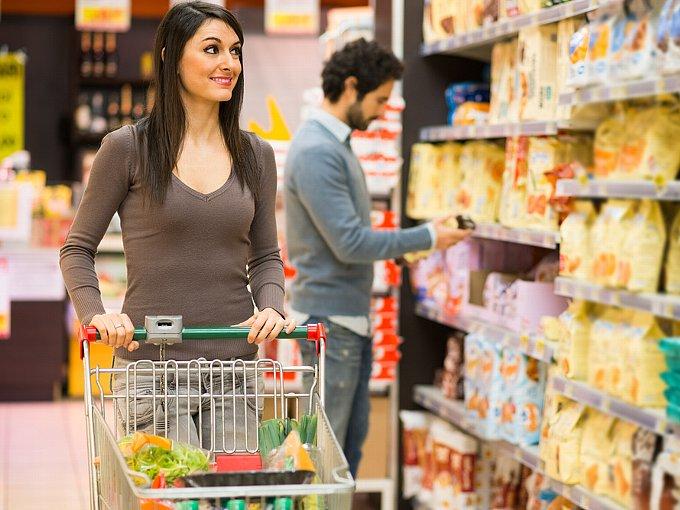 スーパーで商品を選ぶ男性を横目で見る女性