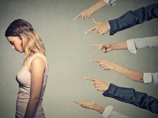 まわりの人に指を差される女性
