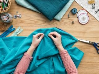 机の上で青い布を縫っている人の画像