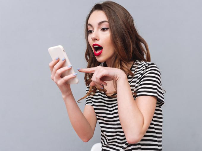 スマートフォンを見て驚いている女性の画像