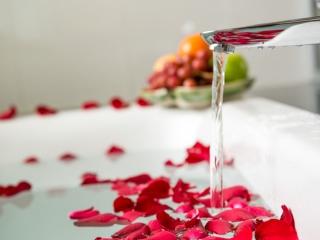バラの入ったバスタブにお湯をためているアップ画像