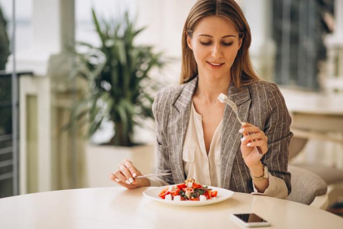 スマホを食べながら食事をしている女性