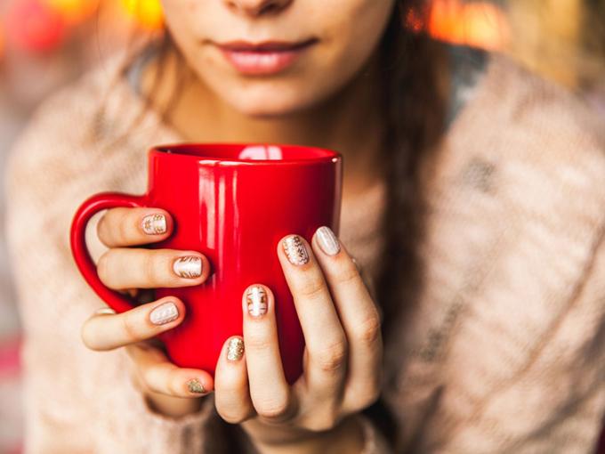 温かい飲み物を飲んで体を温めている女性