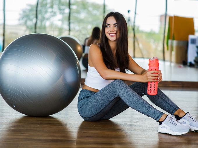 バランスボールの横で休憩をとっている女性の画像