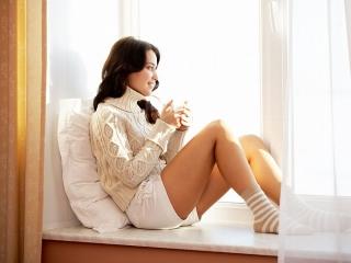 タートルニットを着て、窓の外を眺める女性