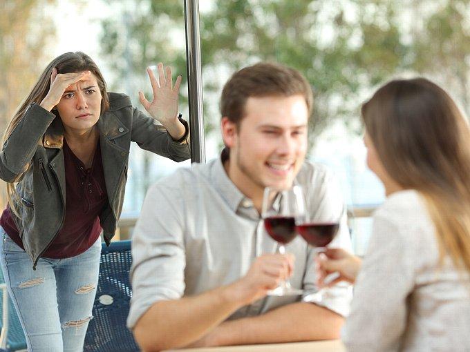 店内で食事をする男女を窓の外から見ている女性