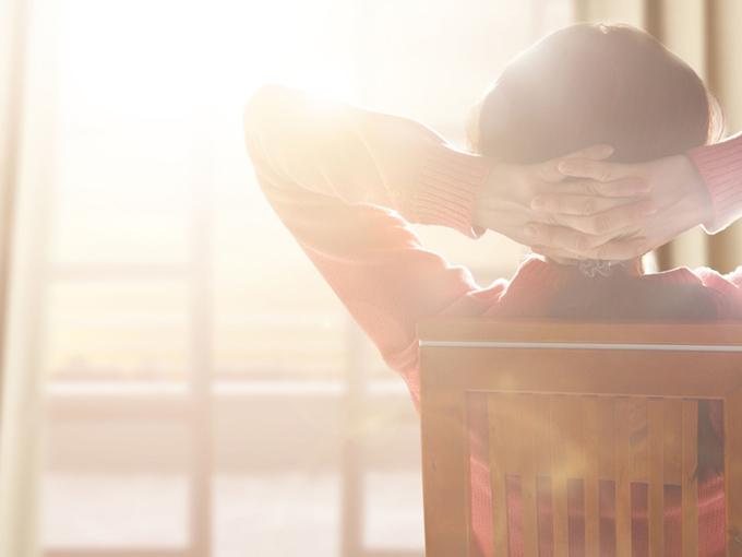朝陽を眺めてリラックスする女性