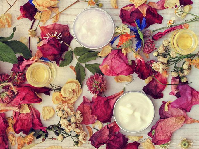 散りばめられた花びらの周辺に瓶に入ったクリーム