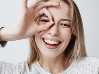 手の間から目を覗かせている女性の画像