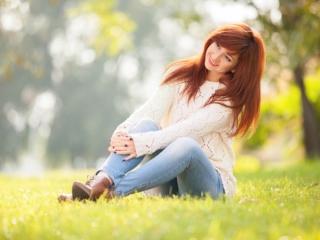 女性が野原に座っている画像