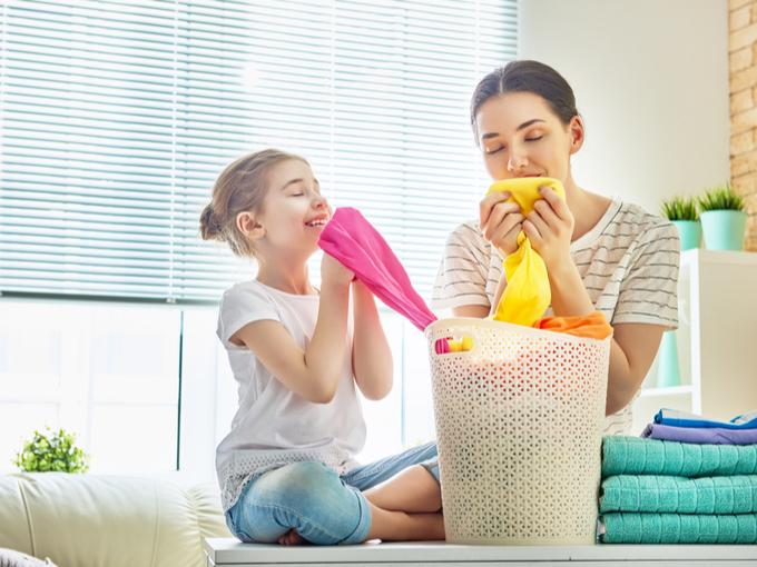 洗濯物の匂いをかいでいる女性と子どもの画像