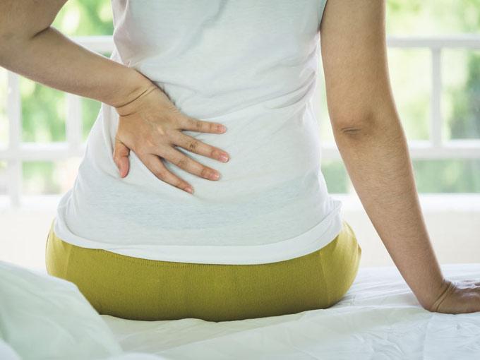 腰を抑えている女性の画像