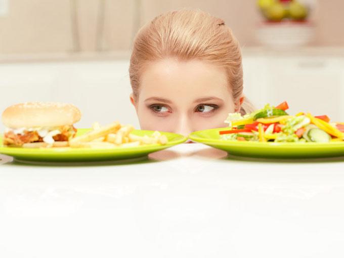 サラダとハンバーガーを見比べている女性の画像