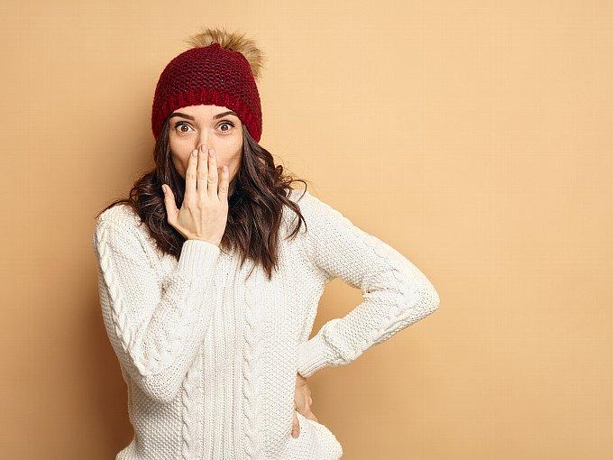 白いニットを着て、右手で口を押さえる女性