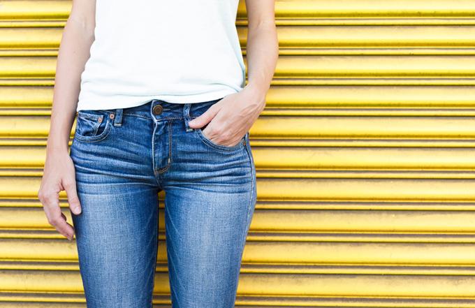 黄色い壁の前でデニムを履いて立っている人の画像