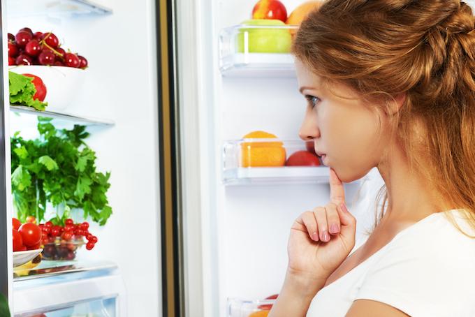 冷蔵庫を開けて悩んでいる女性の画像