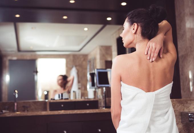 バスタオルを体に巻いた女性が背中に手を回している画像